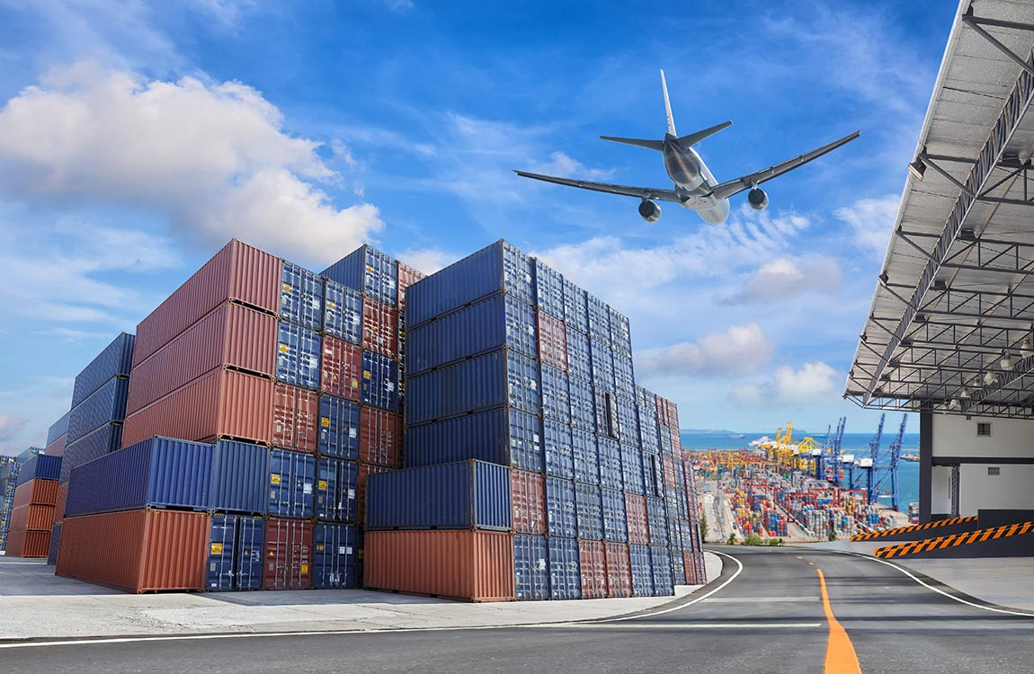 A jet airplane landing at a export facility near the sea, with huge cargo containers stacked on top of each other.